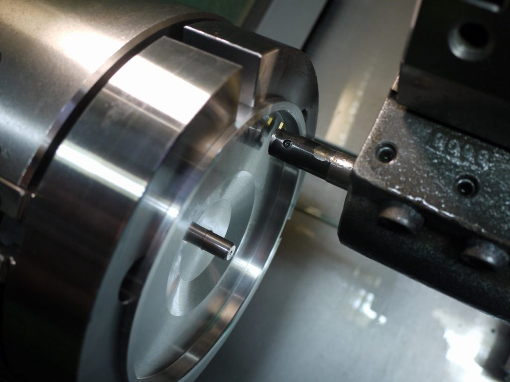 円型生爪でアルミフランジを歪ませないようにチャッキング。NC旋盤でネジのニゲ溝加工。